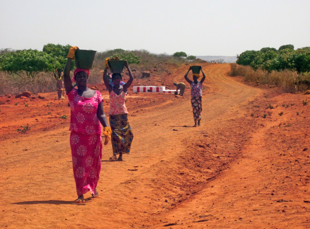 Senegalese women in Keur Moussa transport rocks to construct a dike to control soil erosion in their community