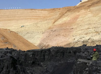 A mine worker looks at stacks of coal in an open-cast steam coal mine located in the Ordos mining district
