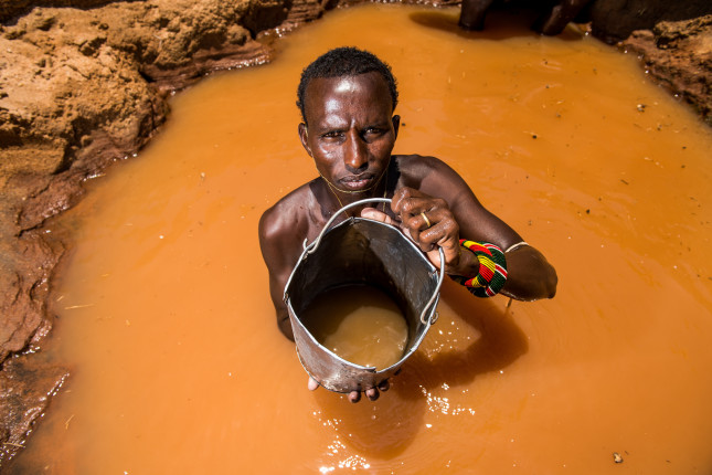 Leparkeri. a Samburu warrior, stands inside a well he has dug along a dry river bed where he will water his livestock during the dry season. They sing as they lift the buckets of water from the deep wells  and each warrior's cattle knows who his owner is