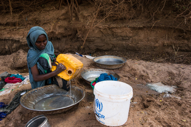 A woman washes her clothes in the Dawa River with three day old water dug from shallow wells in the riverbed, which is now the only source of water for IDP's living in Kansale IDP camp, Somalia, on MAR 24, 2017. The severe drought across Somalia and the Horn of Africa has caused a humanitarian crisis that threatens millions.