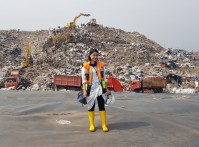 Tiza standing in front of a dumping site