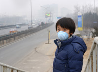 A boy standing with smog